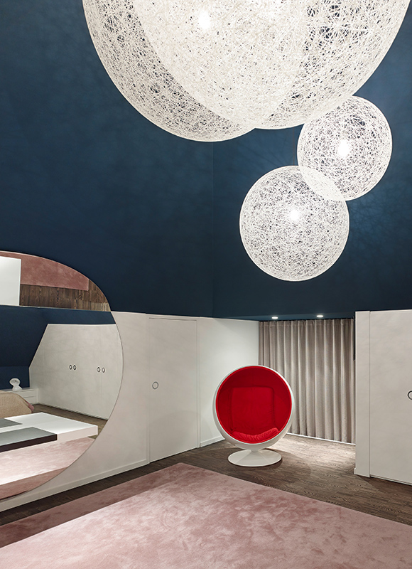 Primary bedroom features a space age look, with floating light spheres in white above red-cushioned egg chair. Dark hardwood flooring contrasts with white walls and dark blue upper layer.