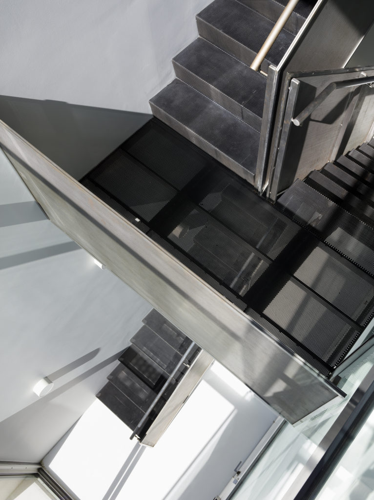 Vertical look straight down the central staircase, highlighting open column for airflow and sunlight.