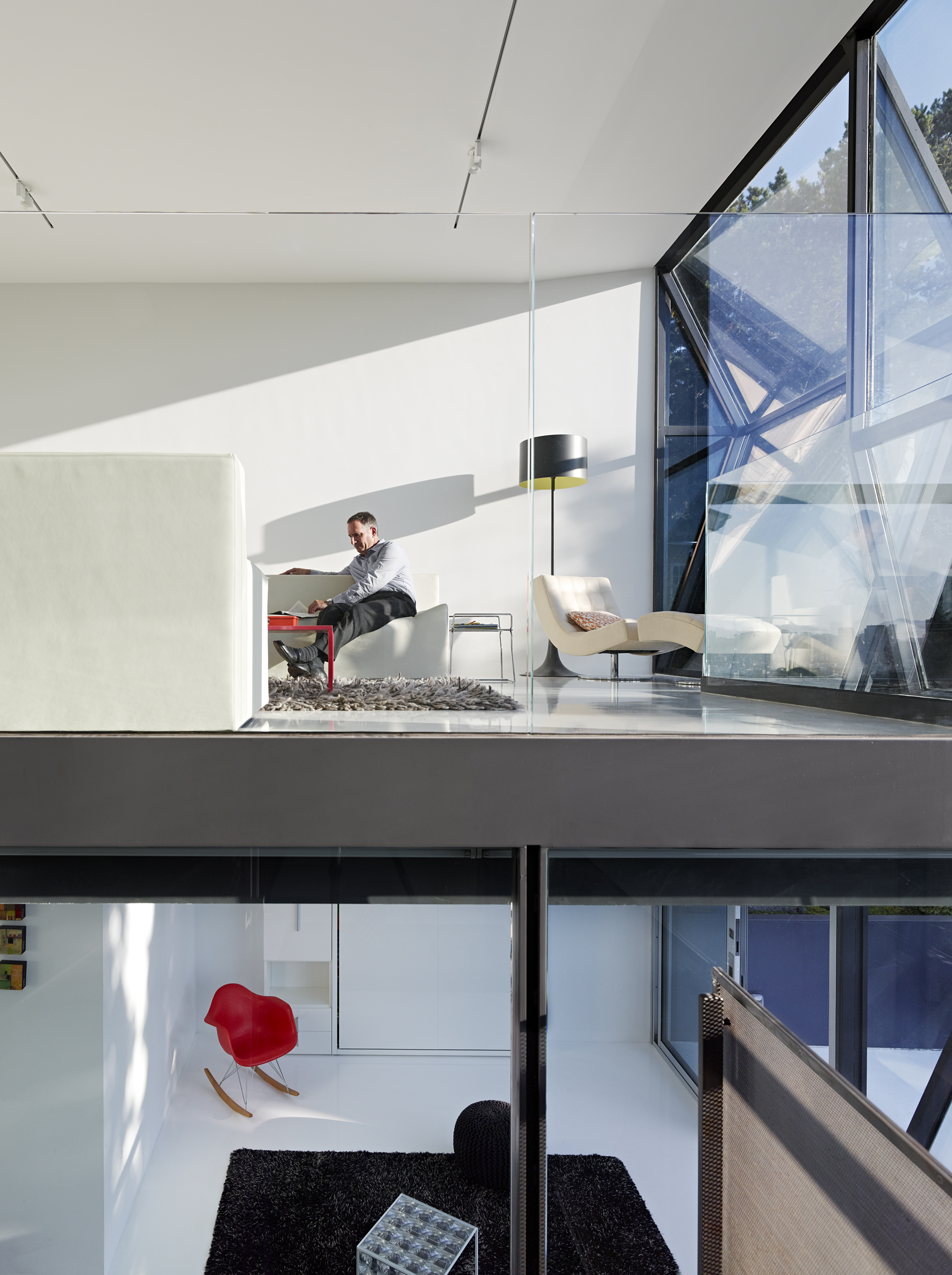This striking side view of the home showcases the minimalist structure, with two layers visible at once. Upper living room features white leather chaise near windows, with all white furniture surrounding grey shag rug and red coffee table. Lower room features black rug and red chair standing out in all white space.