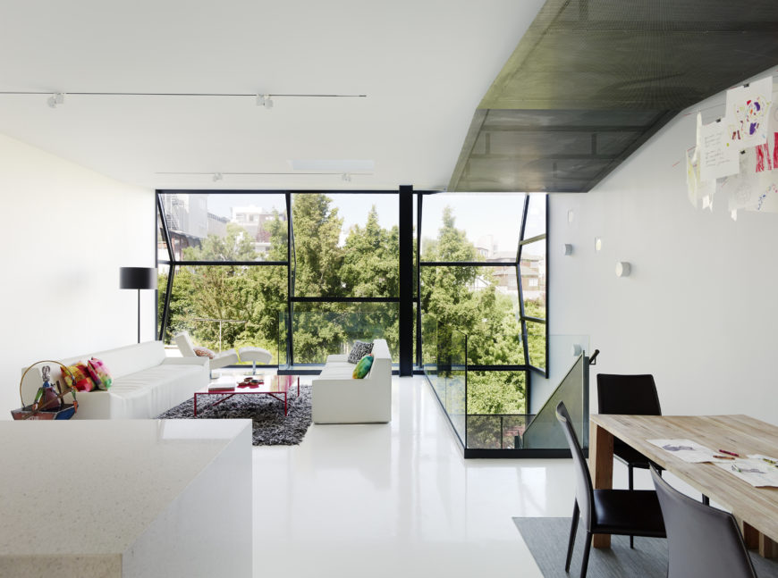 The upper floor as seen from deep within: white spaces throughout, with natural wood dining table over grey rug on right, and marble island on left.