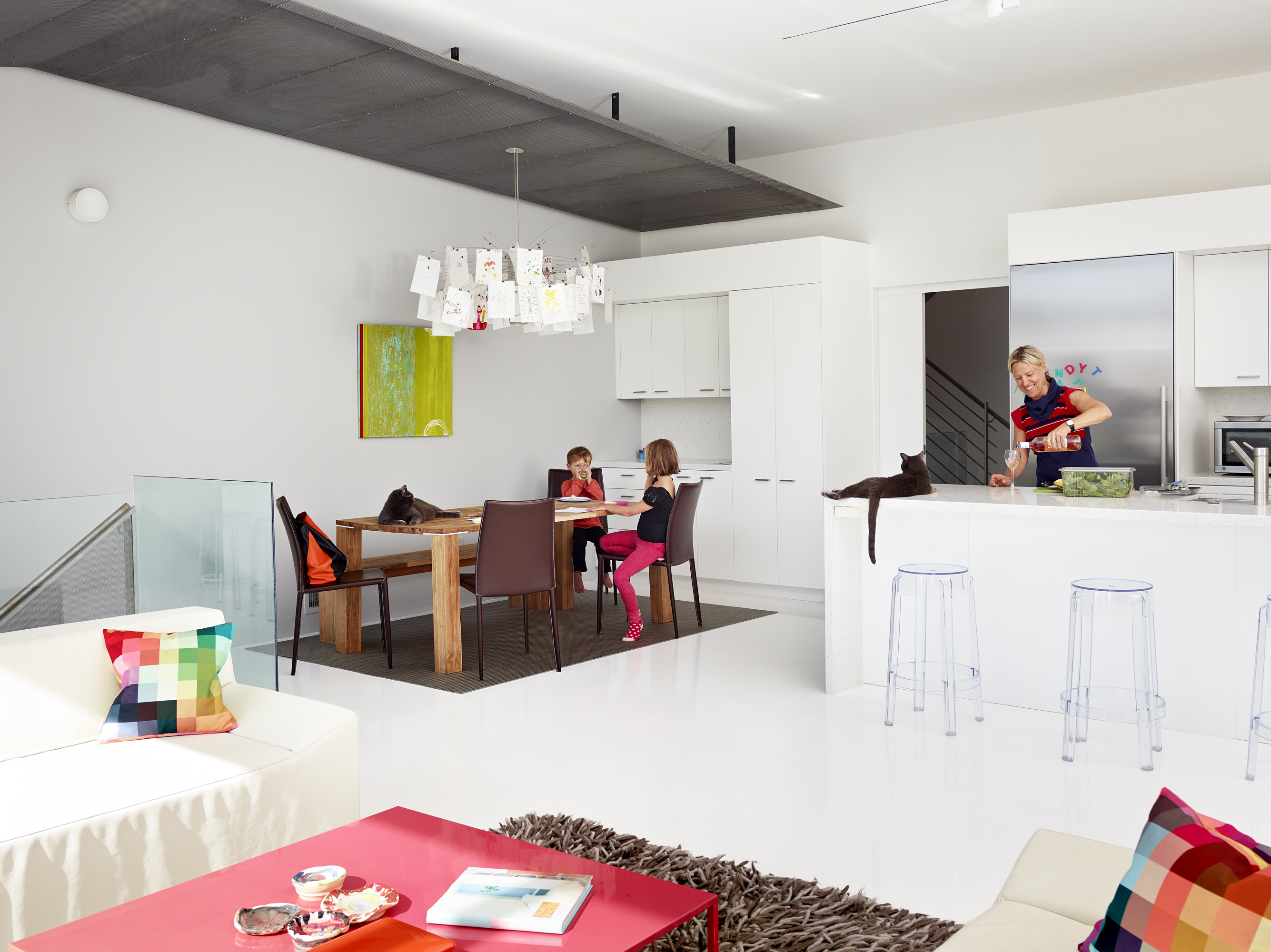 The upper floor as seen from living room space features open design kitchen with white countertops and cabinetry, with transparent plastic bar stool seating at island.