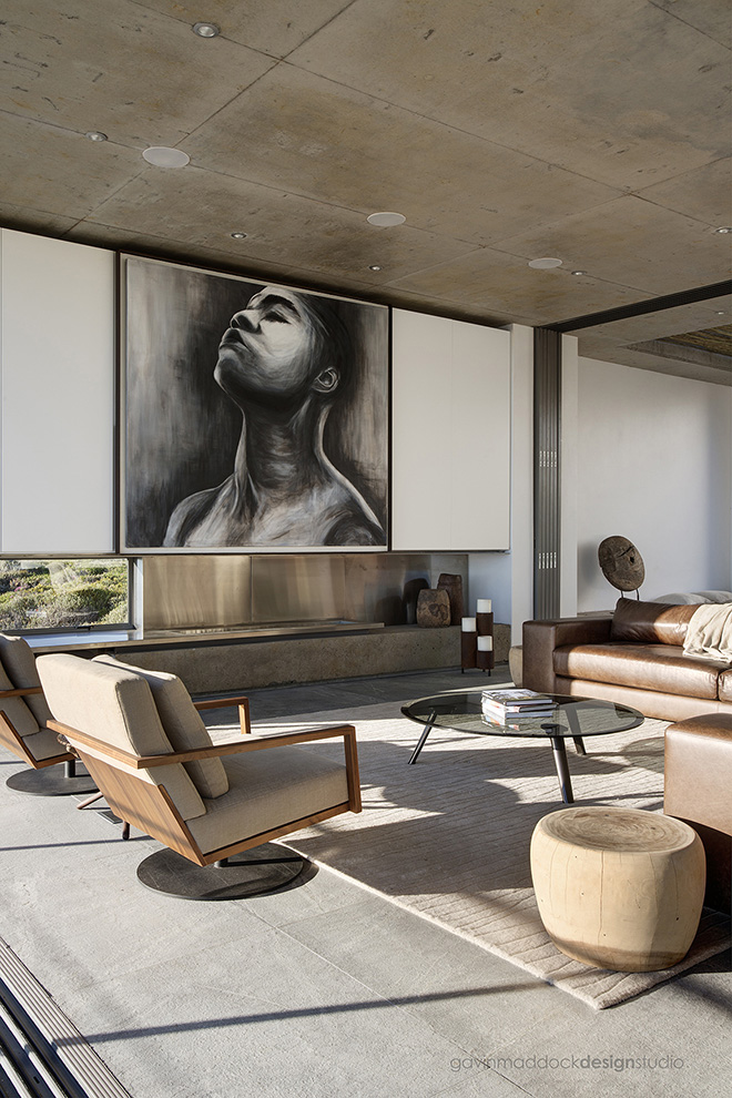 Large art piece towers over the living room, with sand toned area rug defining the space. Contemporary brown leather sectional joins a pair of modern wood and fabric swivel chairs around a modern glass coffee table.