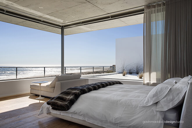 The bedroom overlooks the ocean and rooftop garden at right. Wide chaise lounge sits at the corner for relaxing with expansive views.