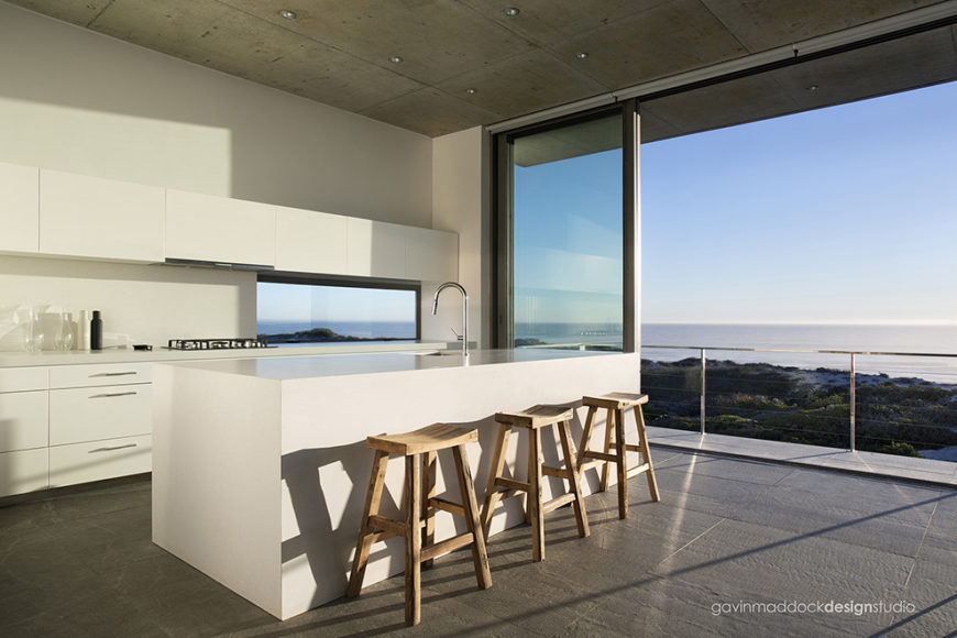 Natural wood stools line up at the large island, with open sliding glass at right joining the kitchen with balcony space. Small slit window over countertop widens the view.