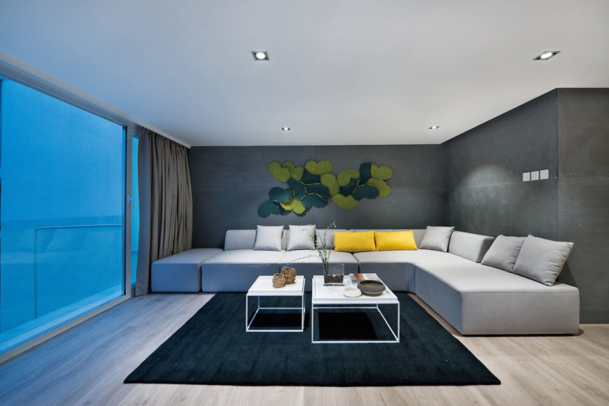 Close view of the second floor living room space. Green toned art piece stands above L-shaped sectional highlighted with yellow pillows, while floor to ceiling glass stands at left, ready to open for patio access.