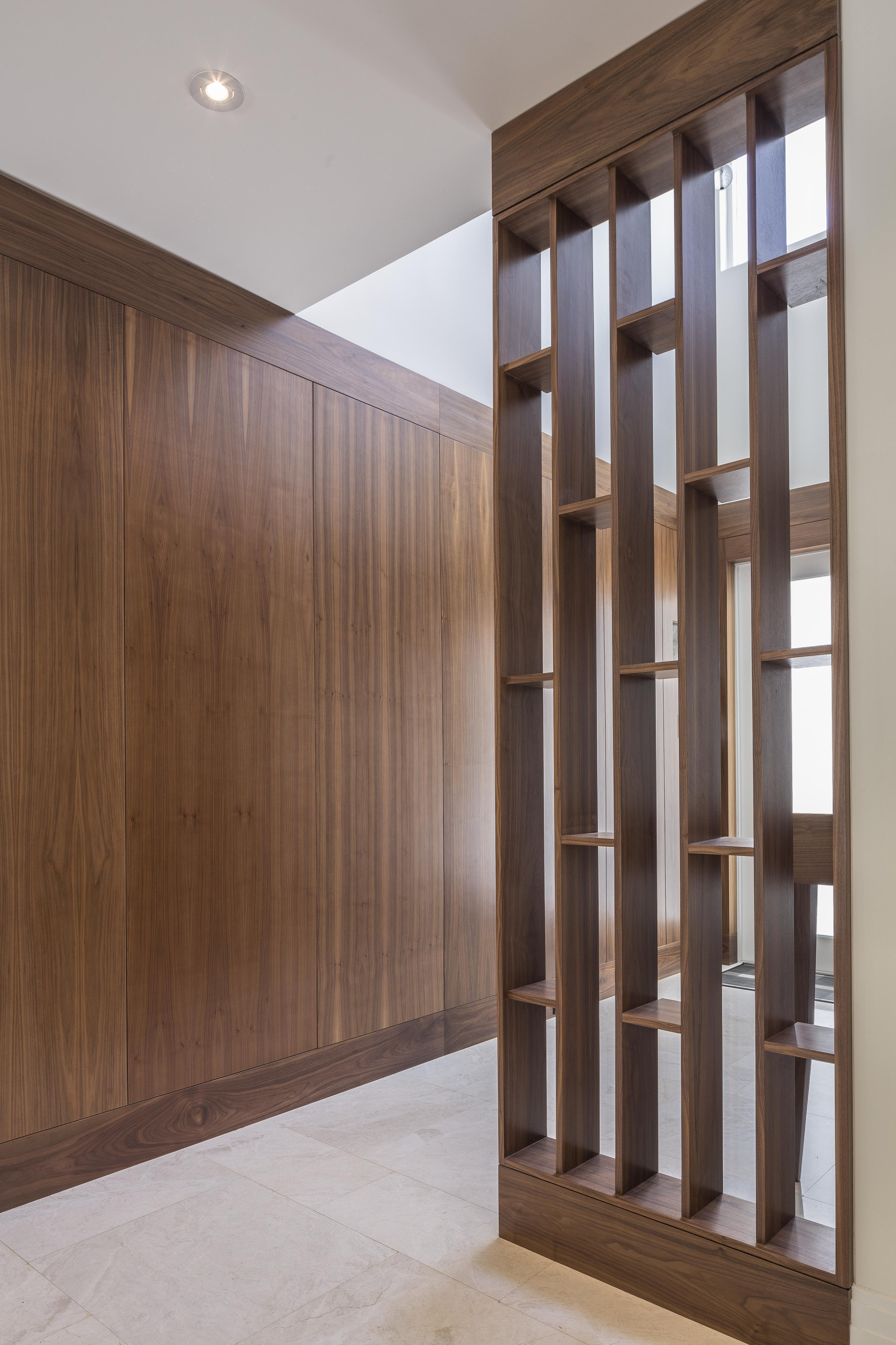 Opposite view of the hallway, showing angular, detailed dividing structure and lush floor to ceiling wood paneling.