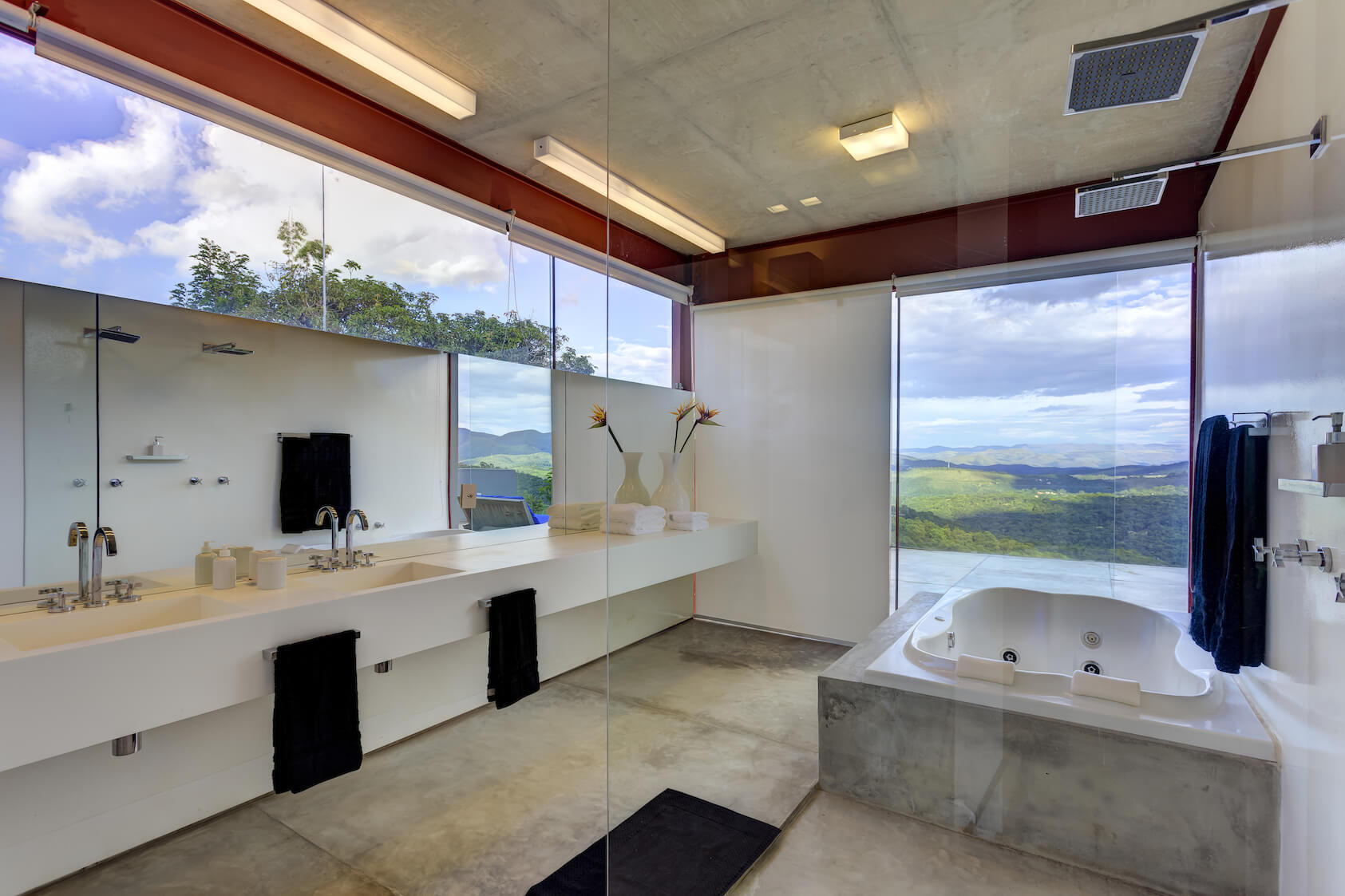 Primary bath reiterates the minimalist, white theme with floating countertop backed by wall-length mirror, seamless glass shower, and large jacuzzi tub next to balcony access.