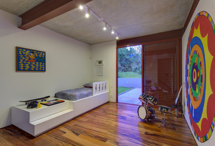 Private area of the home also holds this children's bedroom, replete with built-in white bed structure and shelving. Large, colorful art pieces adorn the walls, while drum set stands beside glass patio door.