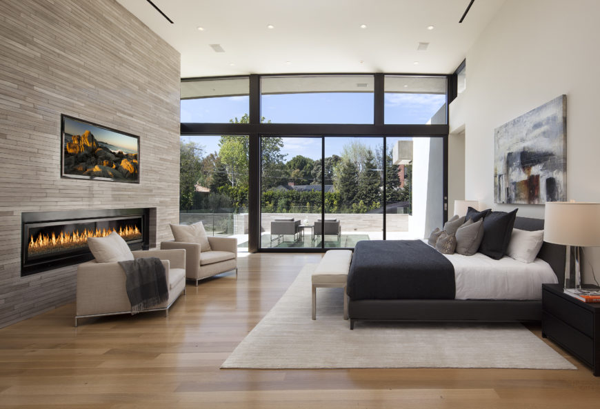 Primary bedroom features another massive gas fireplace and brick surround, with large dark toned bed paired with matching dressers on a beige area rug. At the rear is another large sliding glass panel, allowing access to the furnished upper level patio.