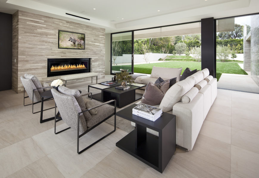Lower level family room wraps large white L-shaped sectional and twin metal frame armchairs around a cubic black coffee table, in front of massive gas fireplace surround. Floor to ceiling glass allows for expansive views over back yard.