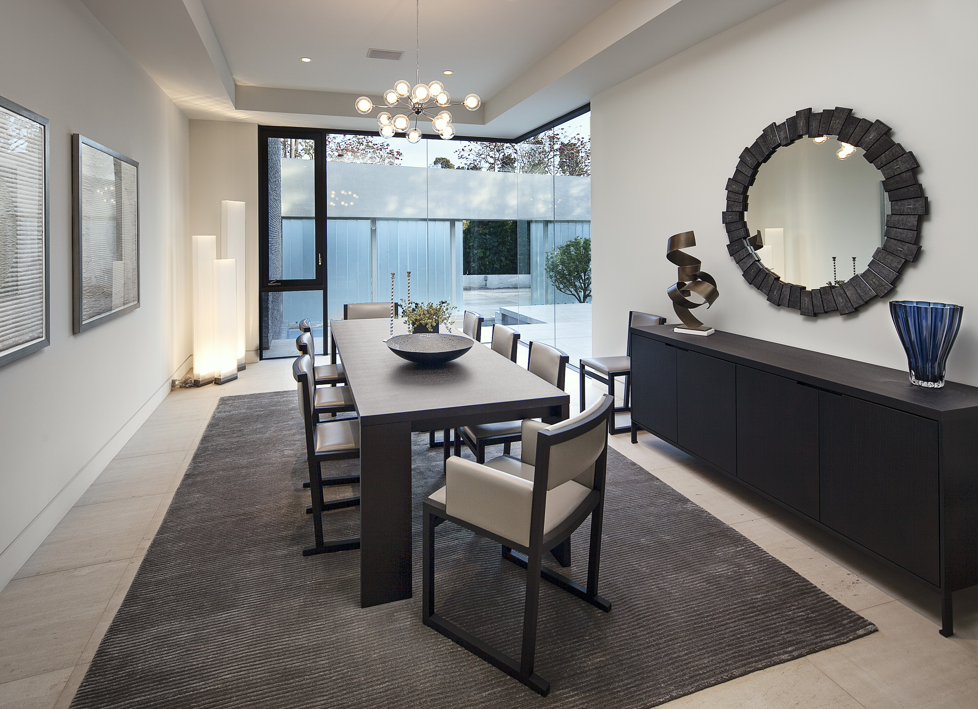 Formal dining room features elegant, lengthy dark wood table with matching cabinetry, unique art pieces scattered throughout, and pristine view toward the front courtyard.
