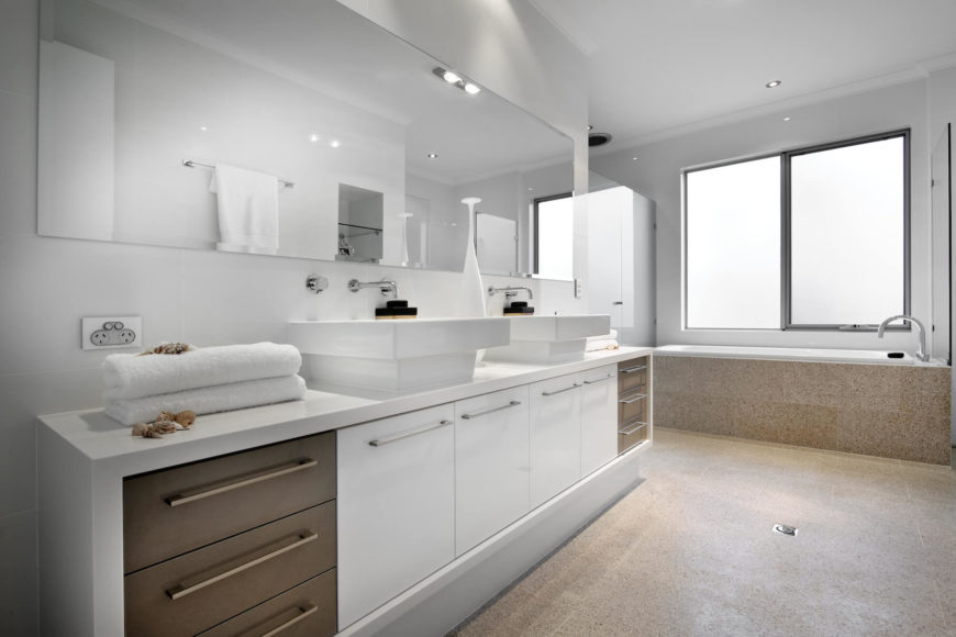 Primary bath features more of the beige marble flooring, with white countertops and cabinetry contrasting with brown toned drawers at opposite ends of the large vanity holding twin vessel sinks.