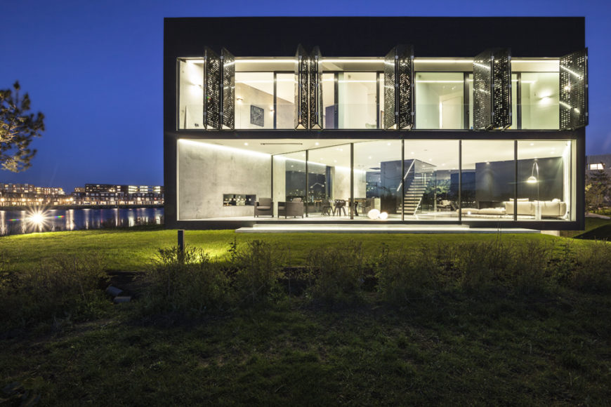 Head-on view at night time showcases the incandescent interior through glass lower facade and fully open steel shutters above by Studioninedots.