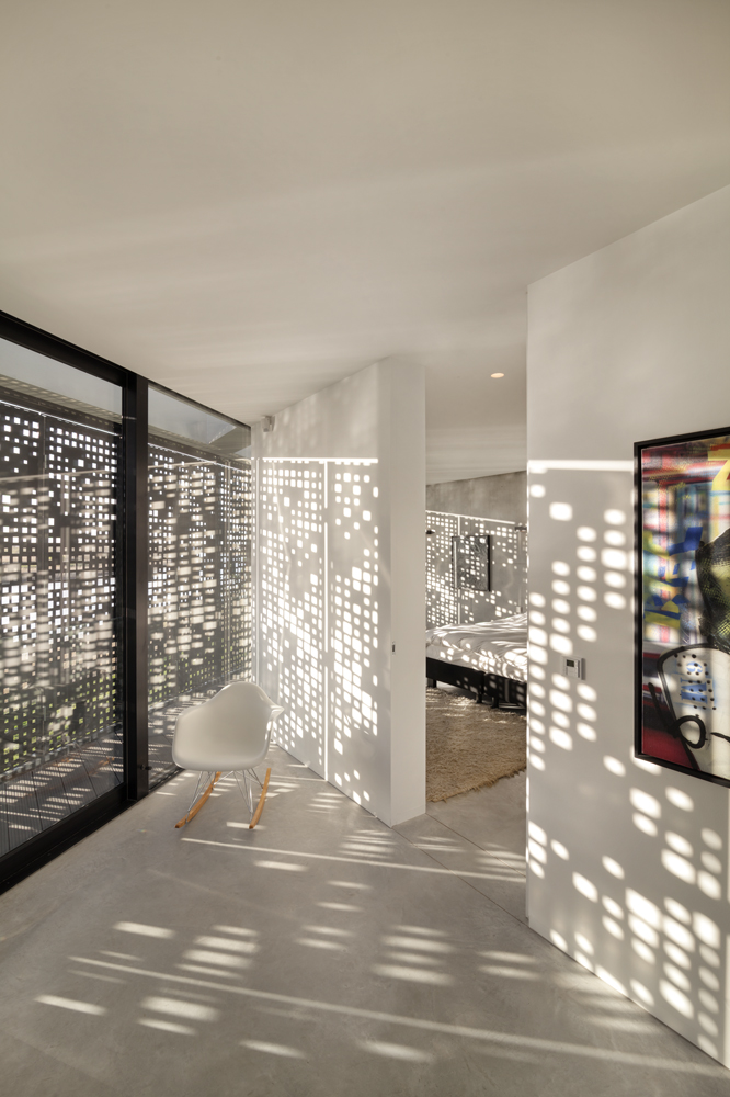 """The """"code"""" patterned shutters provide moments of striking dappled sunlight throughout the home, as seen in this view of the upper hallway and bedroom."""