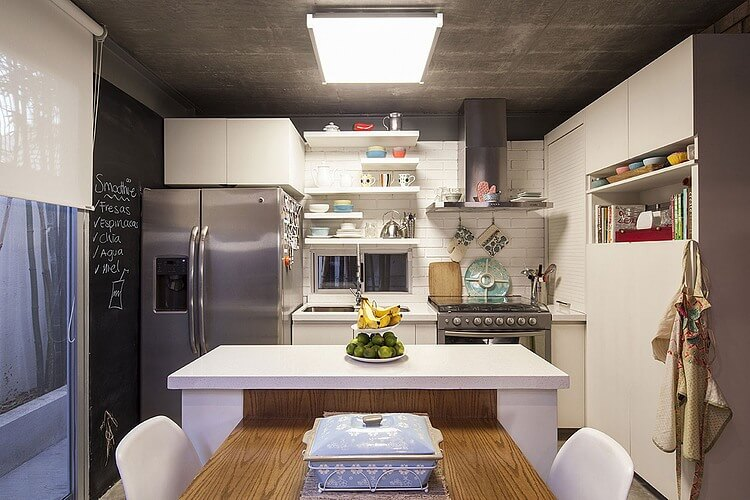 The cozy kitchen maximizes its space with clever combination of dual-use island with natural wood dining space, while white brick and countertops pair with steel appliances in background.