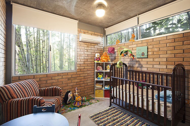 Children's room features shaded windows with views of the bamboo on two sides, plus large dark wood crib and striped armchair, as well as the requisite toy storage and small colorful table.