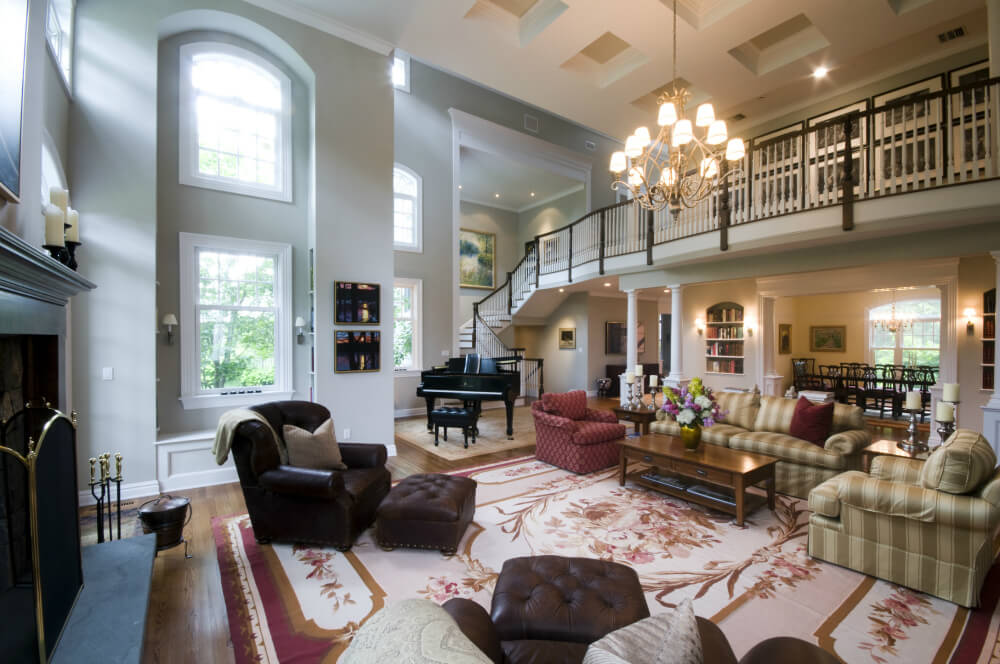 Massive two story living room centered around red floral area rug, featuring dark leather chairs and striped sofa set, hardwood flooring, grand piano, and massive fireplace. Lengthy catwalk hallway overlooks the space lit with natural light via full height windows.