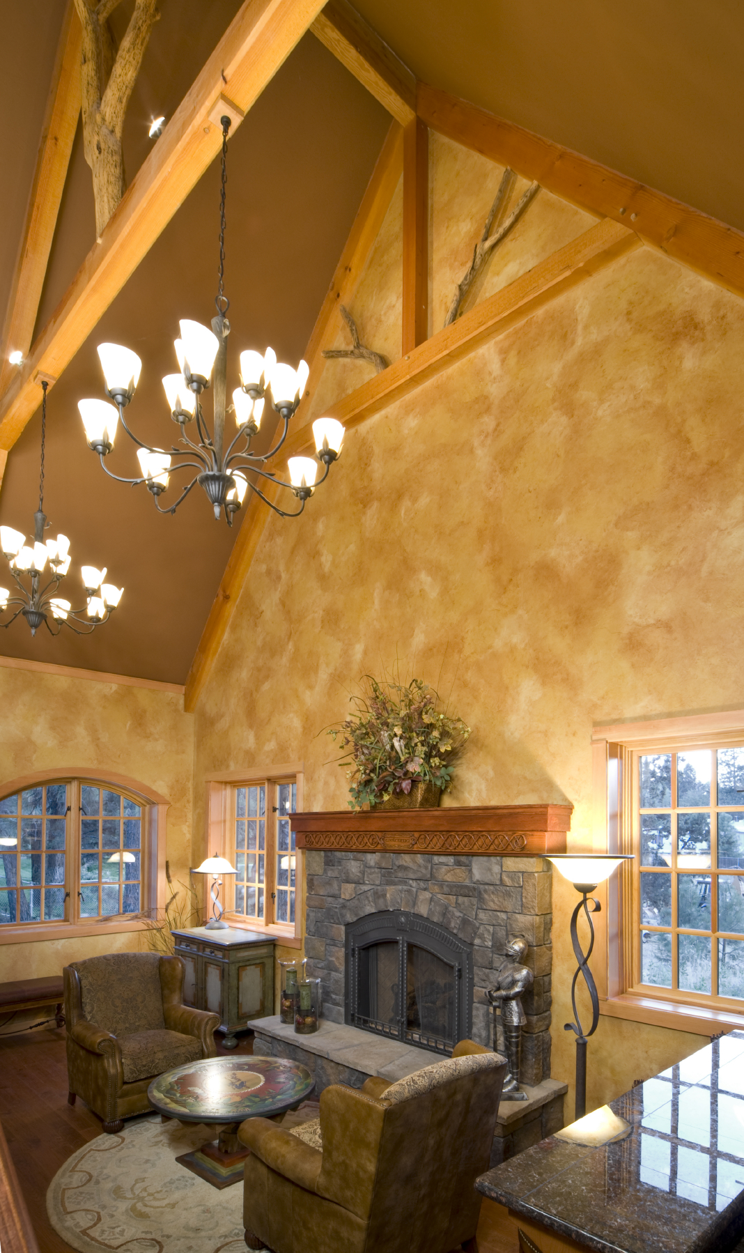 Soaring vaulted ceiling with exposed natural wood beams hovers over this cozy space, with large stone fireplace standing before a pair of leather roll arm chairs and painted circular coffee table.
