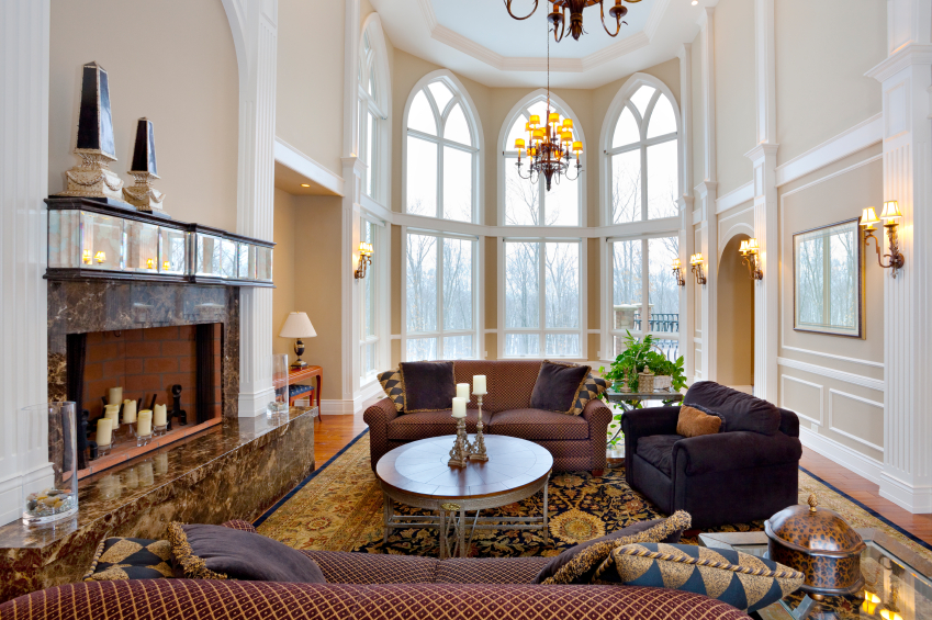 Soaring white detailed ceiling hangs a lamp style chandelier over this living room, featuring warm hardwood flooring, brown marble fireplace with glass and wood mantle, and twin patterned sofas facing over circular wood coffee table.