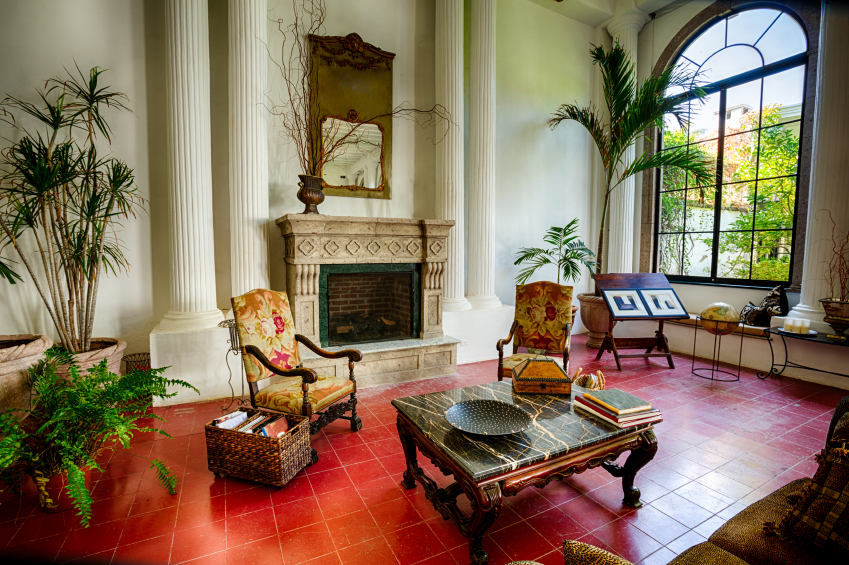 Unique red tile floor holds this ornate living room, touched with safari details like greenery and carved fireplace surround. Massive windows allow natural lighting throughout, while marble topped, ornate coffee table stands at center.