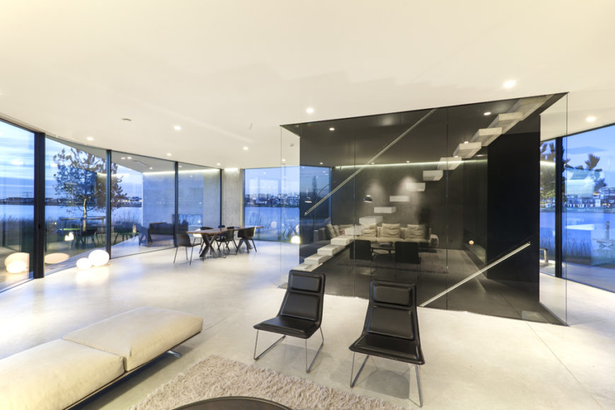 The living room features not only the low-slung modern white sofa, but a pair of modern black chairs, reflecting the black-and-white contrast of the wider interior.