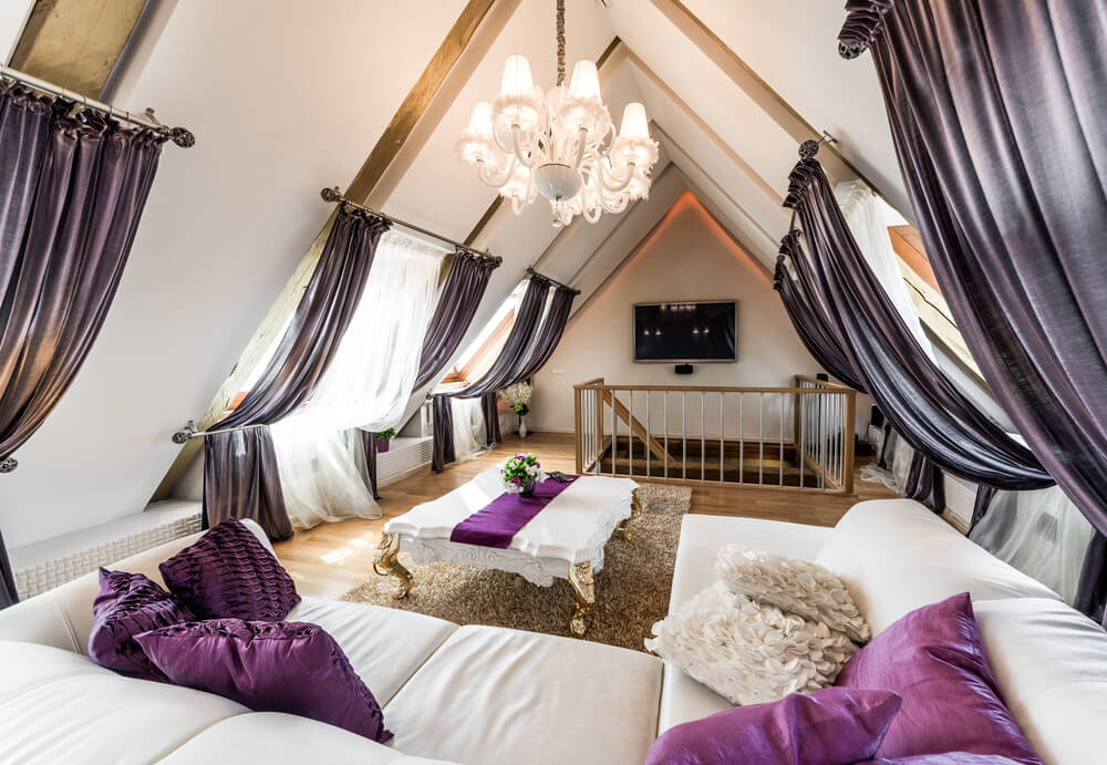 Top floor living room filled with lavish employment of purples and whites: decorative curtains hang from angled sky light windows, white leather sofa dappled with purple throw pillows, gold-legged, and white marble coffee table decorated with a single purple stripe of fabric.