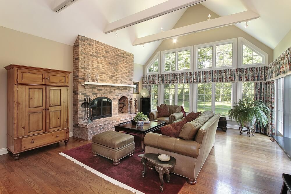 Traditional styling in this living room includes red brick fireplace with built-in wood storage, natural wood cabinet over hardwood flooring, and brown leather sofa set wrapping around dark wood table. Full height windows cover the arched wall at back.