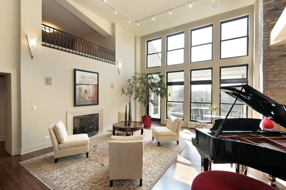 Contemporary styled living room mixes dark wood flooring, beige walls, and black details - wrought iron catwalk railing, window frames, and grand piano - with a set of white chairs arranged around circular wood coffee table, next to array of windows overlooking balcony.