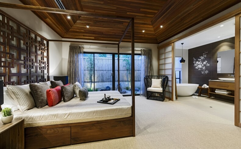 Vaulted timber ceiling soars over primary bedroom suite, featuring natural wood canopy bed across from shoji screened private bathroom with white pedestal tub and black vanity wall with floral art print.