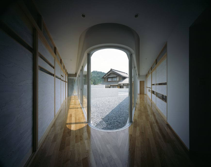 This view is from the center of the V structure of the home, with mirrored hardwood hallways reaching toward each end. Floor to ceiling glass on this side of the home illuminates throughout, with spectacular views facing toward the mountains.
