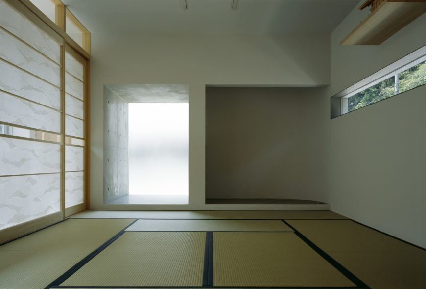 Interior rooms feature mat flooring, white walls, and natural wood accents throughout, including high shelf above slit window on right.