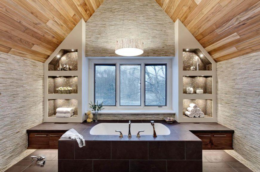 Un plafond cintré en bois naturel frappant est suspendu au-dessus de ces deux salles de bains, avec une baignoire encastrée dans une enceinte de tuiles avec des armoires en noyer intégrées, flanquées d'étagères ouvertes remplies de carreaux avec éclairage intégré.