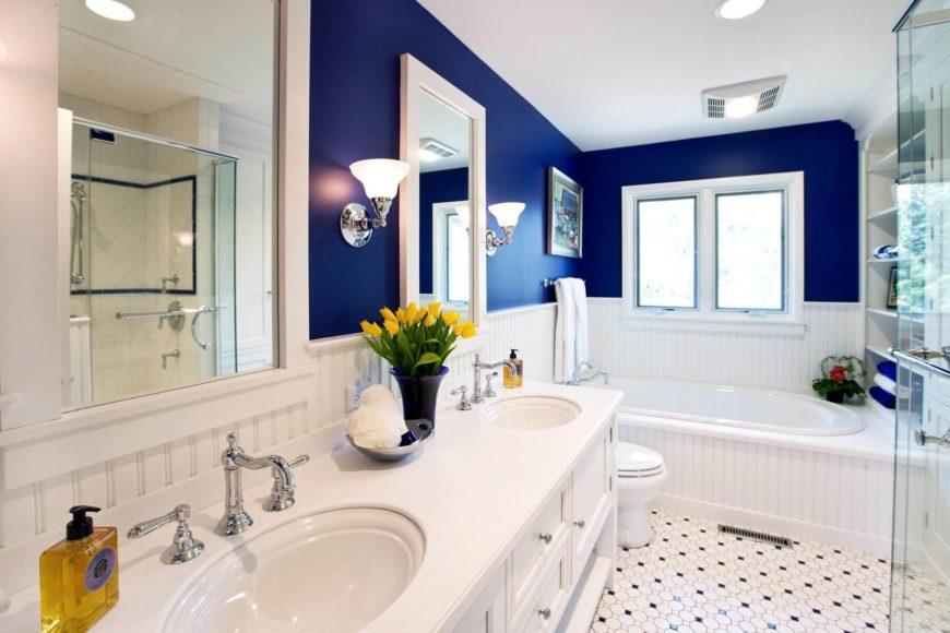 Le schéma bleu et blanc frappant encadre cette salle de bain confortable, avec une double vanité blanche flanquée d'appliques murales chromées.  Le grand bain à remous se trouve sous les fenêtres à l'extrémité, avec une douche entièrement en verre à droite.