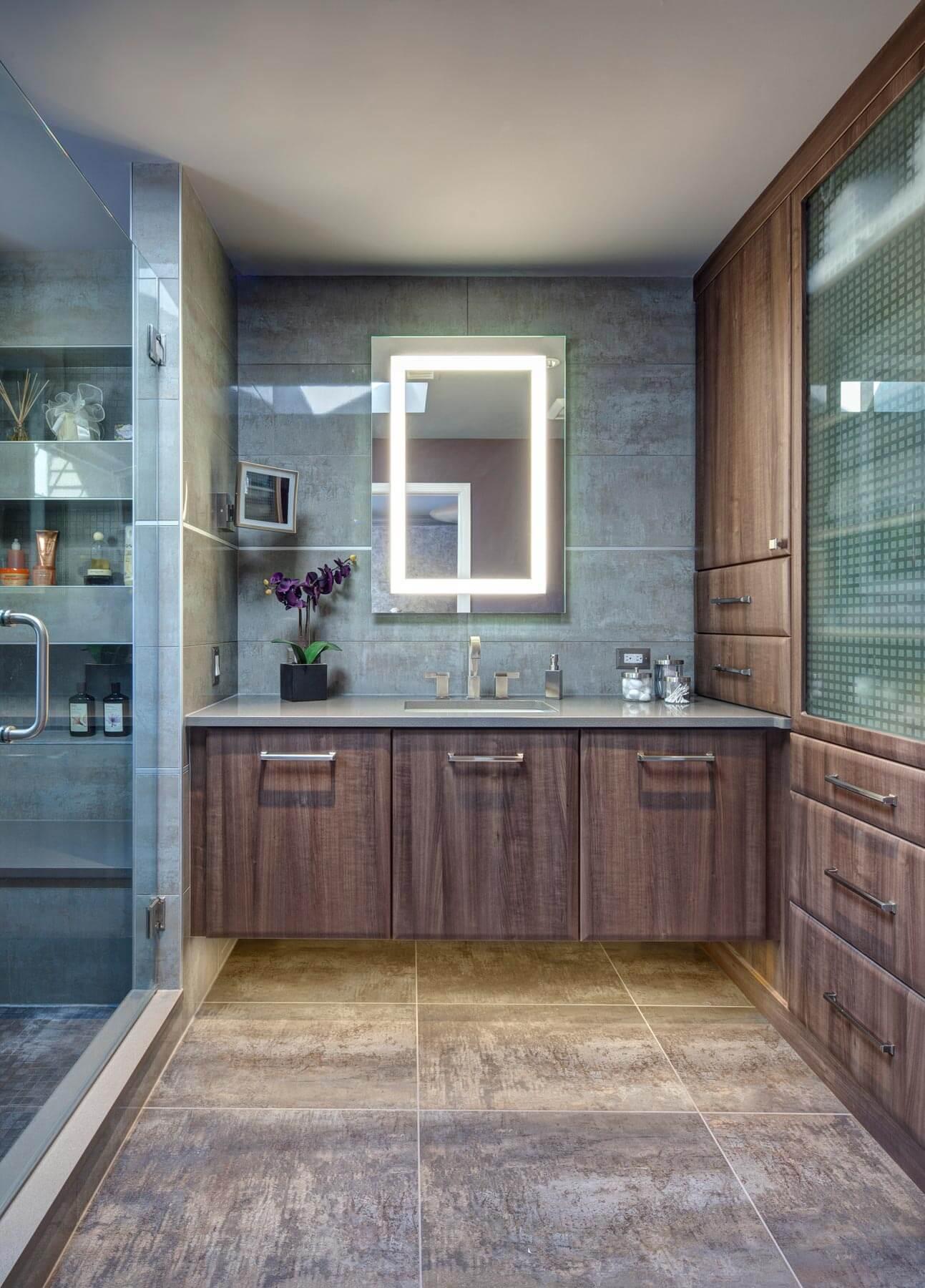 La salle de bains présente des matériaux de couleur naturelle de grand format et un miroir de courtoisie avec éclairage intérieur.  Une palette de marron et de bleus apaisants a été utilisée dans cette salle de bain principale nouvellement rénovée, tandis que la fonctionnalité a été ajoutée via une gamme de rayonnages de douche et d'armoires.