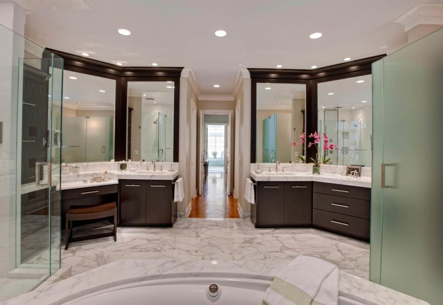 """Espresso cherry wood cabinetry and thick slab countertops define a set of """"his and hers"""" vanities flanking this expansive bathroom, replete with marble everywhere. All glass shower stalls stand aside the large jacuzzi style tub at center."""