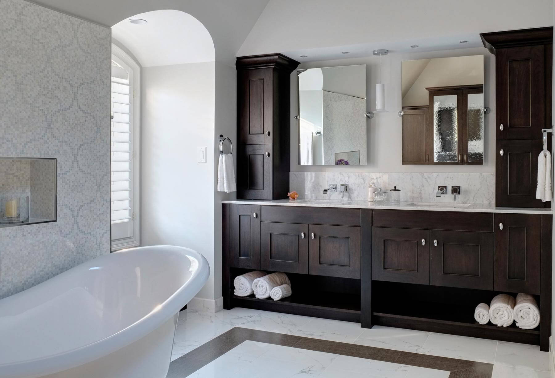 Le contraste entre les armoires en hickory foncé et le marbre clair définit cette grande salle de bain ouverte.  Le mur de carreaux de mosaïque se trouve à côté de la baignoire blanche sur piédestal, tandis que la double vanité avec miroirs inclinables flotte au-dessus du dosseret en marbre.