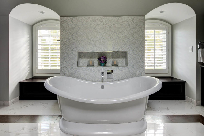 The free standing soaking tub commands attention at the center, before a patterned tile wall flanked by a pair of bay windows with storage beneath.