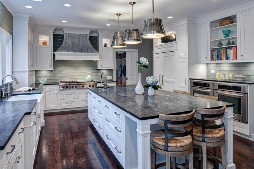 The immense island matches the surroundings, with white painted wood cabinetry and black quarzite countertops. A small dining space sits opposite the range area, with its soft glass tile backsplash.