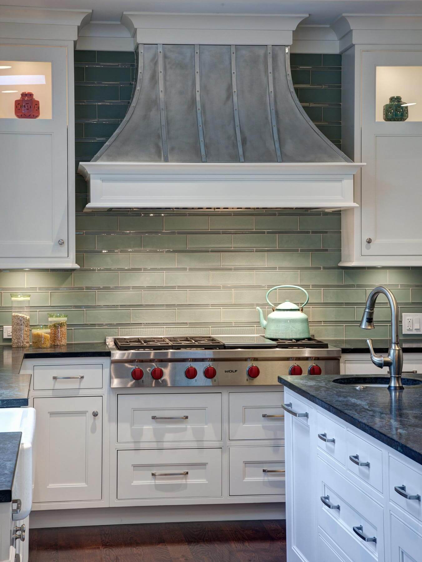 The extra large range is defined by the soft green tone of the tile backsplash, beneath the custom crafted metal hood. Island features a secondary sink, at right.