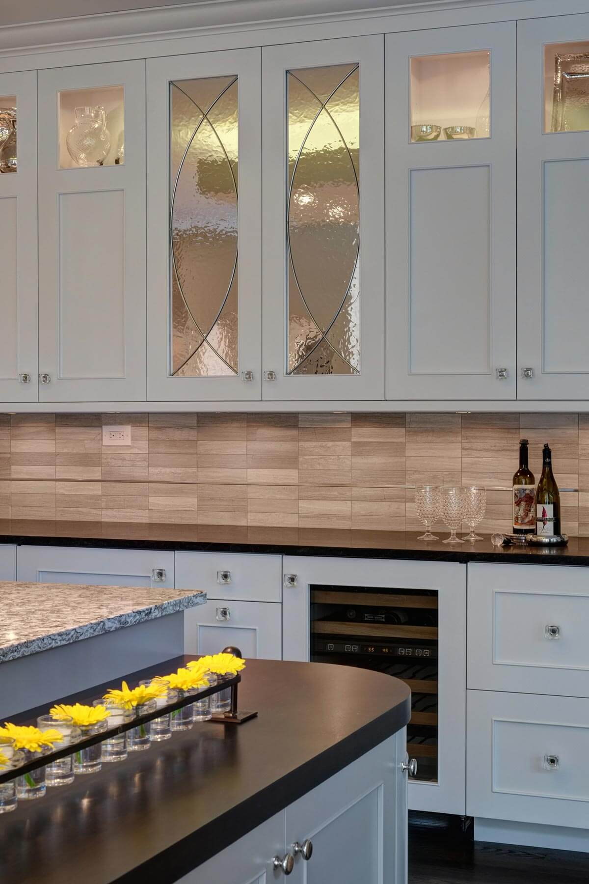 "Lower tier on the ""homework"" island features matching black granite countertop and rounded edges. Above the countertops we see the stone backsplash with single strip detail."