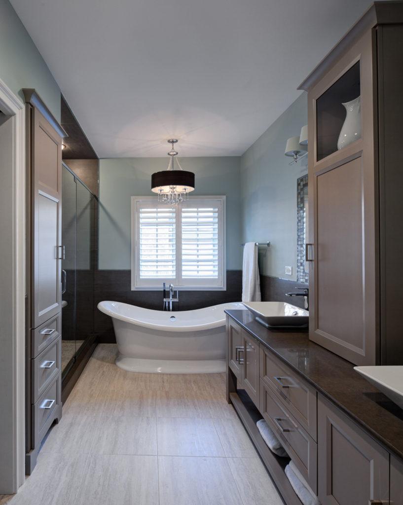 La longue salle de bain étroite est remplie d'armoires peintes en taupe et de carreaux de sol en pierre, avec des carreaux de mosaïque enveloppant les miroirs de courtoisie à droite, suspendus au-dessus des éviers angulaires blancs.  Des étagères cachées se trouvent sous les tiroirs, tandis que la baignoire piédestal blanche incurvée brillante attire l'attention au centre.