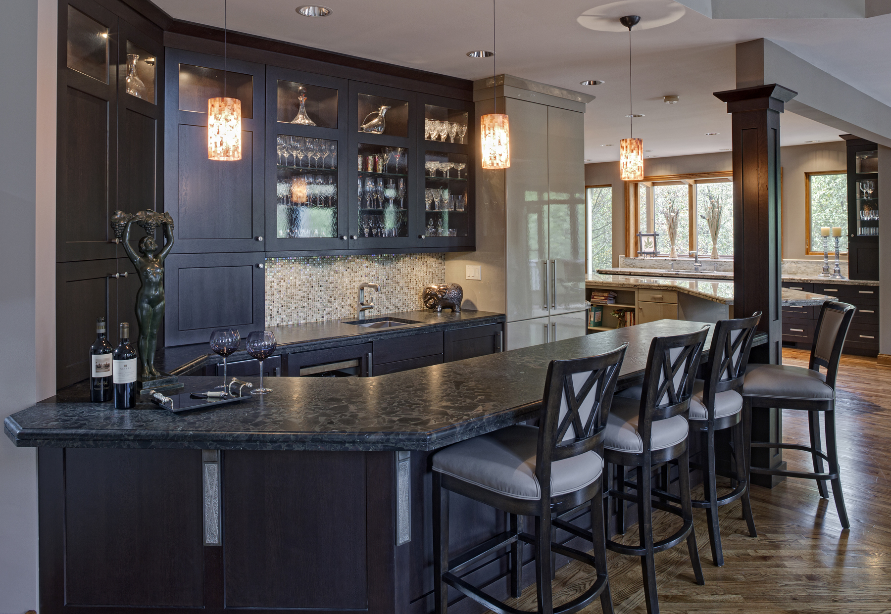 The dark espresso finished wood features throughout the wet bar and upper, glass-panel cabinetry. An array of dark wood seating stands before the single column dividing the space.