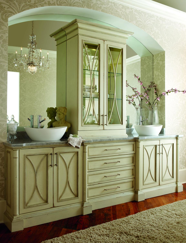 Habersham Cabinetry a conçu cette magnifique vanité double avec des armoires en bois traité, des éviers blancs et un comptoir en marbre.  L'armoire à porte en verre divise le miroir mural massif unique au centre.