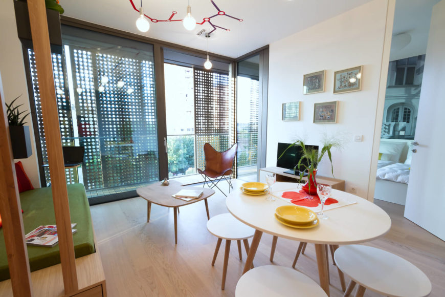 The open living space stands the dining table and matching circular chairs at center, with natural light streaming through the slotted shades wrapping the balcony behind sliding glass.