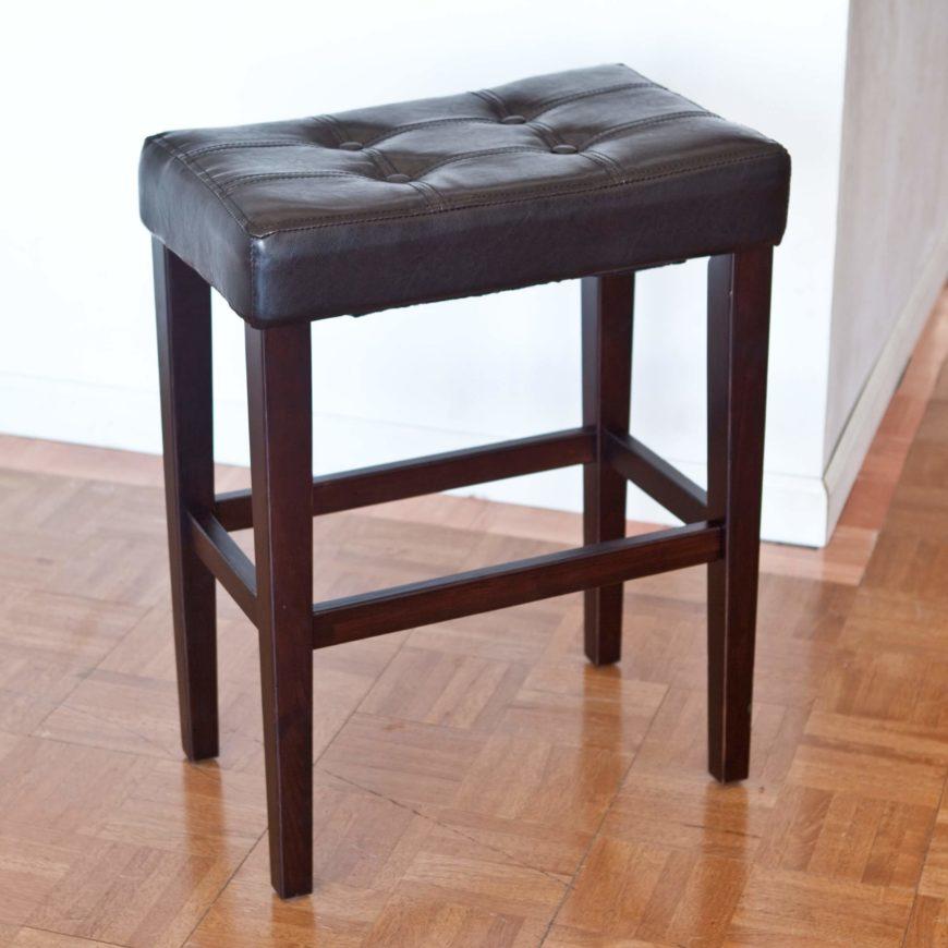 Basic saddle style stool with wood legs and black upholstered seat.