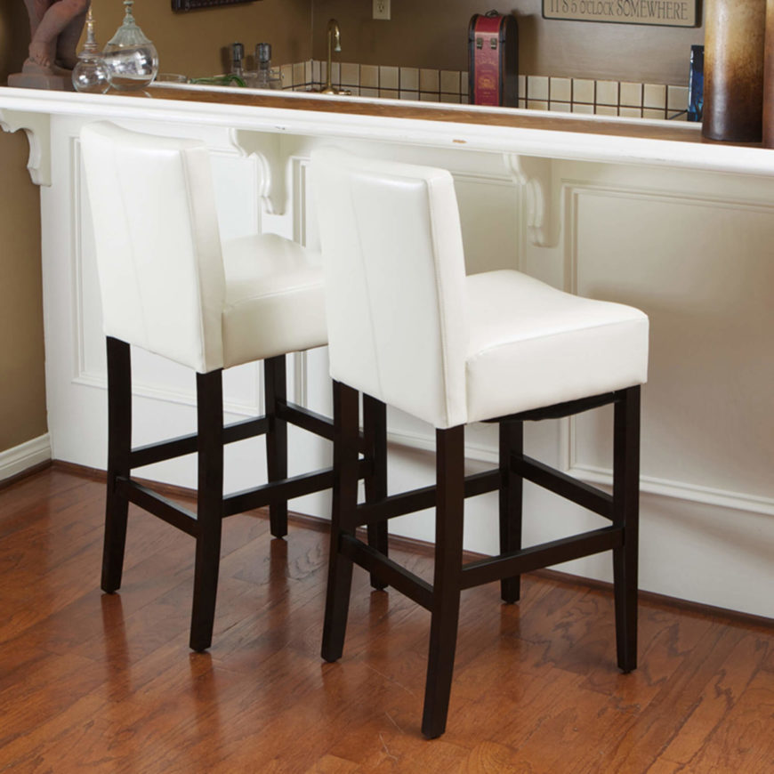White leather counter stools with wood exposed wooden legs.