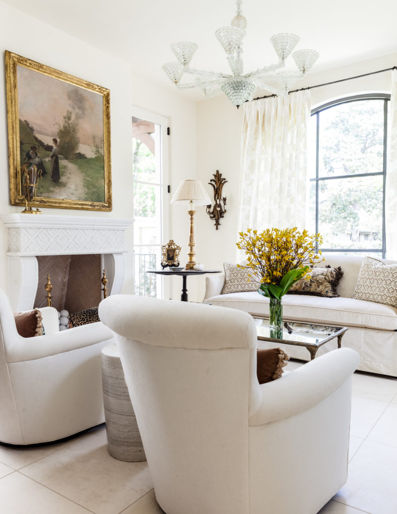 A white marble fireplace matches the bold, bright surroundings, with large painting above adding color to the room.