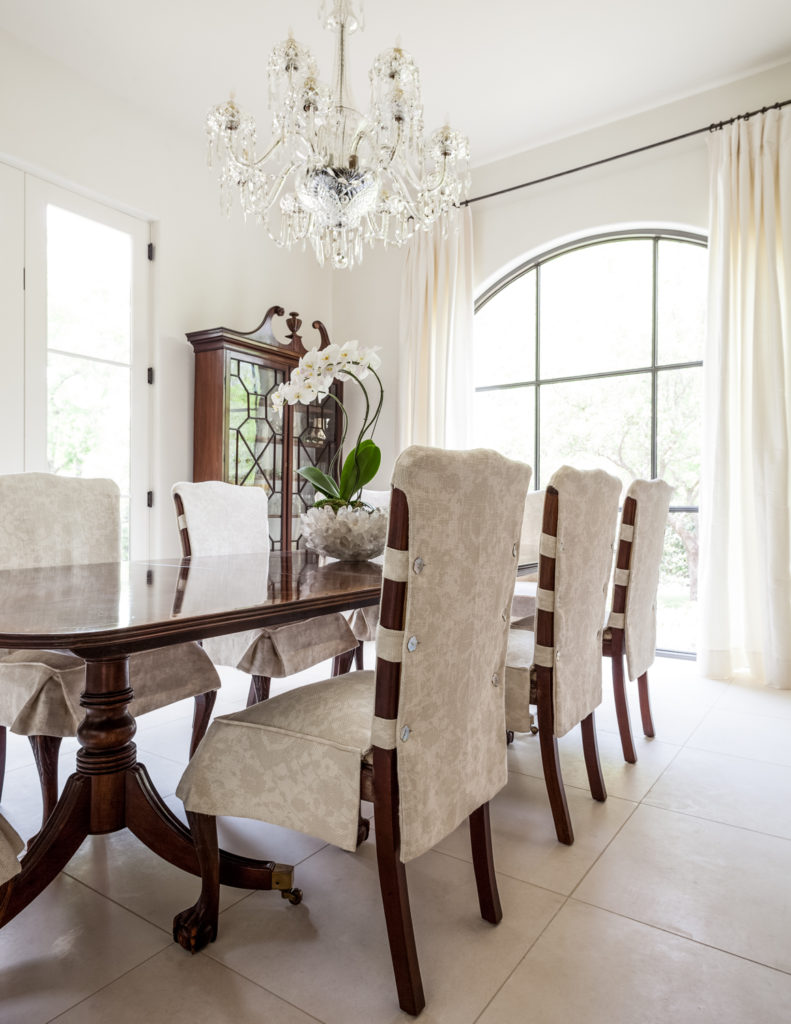 Large format white tile flooring continues in here, lending the deep rich wood table and chairs a sense of contrast.