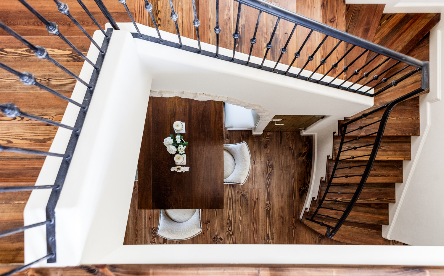 A vertical view down to the first floor reveals an expanse of rich natural wood tones on the stairs, contrasting sharply with white walls and wrought iron railing.