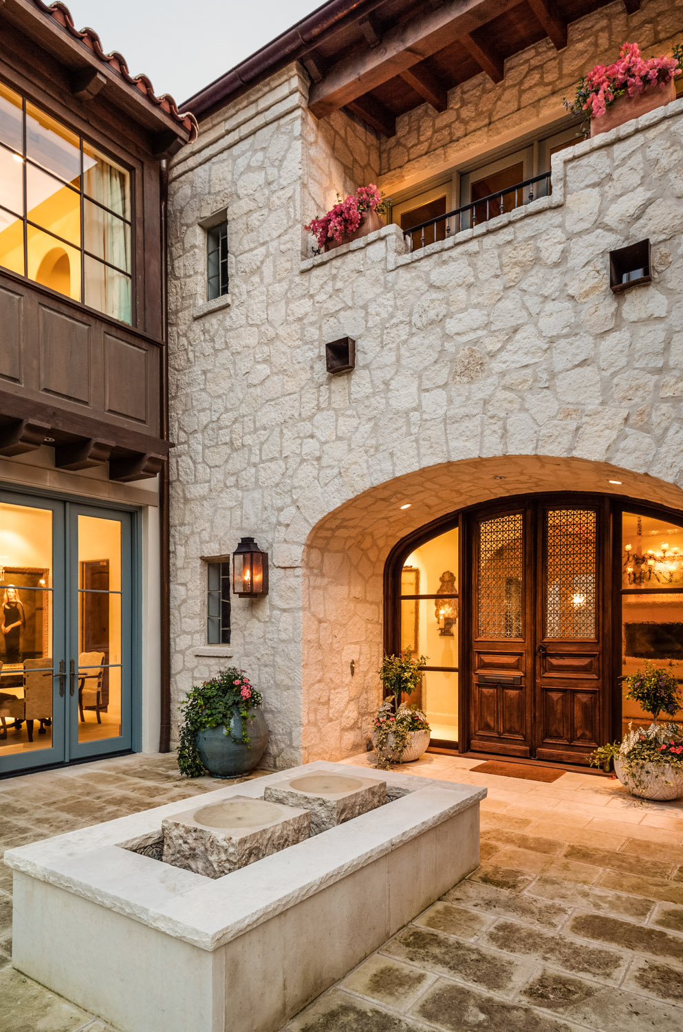 This broad, open entryway sets a double wide door beneath a stone arch, with partially obscured balcony overhead. Large stone bricks wrap a central fountain before the wood doors.